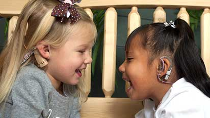 Two girls with cochlear implants smiling at each other