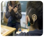 Child with cochlear implant watching sign language