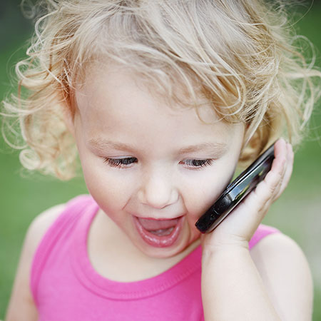 Toddler girl pretending to talk on the phone
